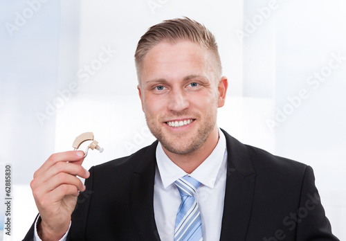 Businessman holding hearing aid