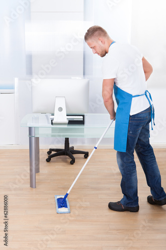 Janitor cleaning the floor in an office building