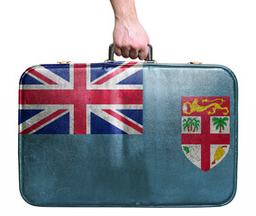 Tourist hand holding vintage leather travel bag with flag of Fij