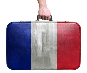 Tourist hand holding vintage leather travel bag with flag of Fra