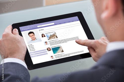 Close-up Of Man Browsing On Digital Tablet