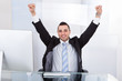 Businessman With Arms Raised Sitting At Computer Desk