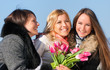 Three beautiful young women with pink tulips