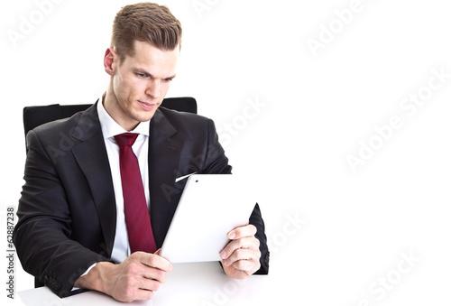 Hübscher Mann im Anzug liest auf Touchscreen