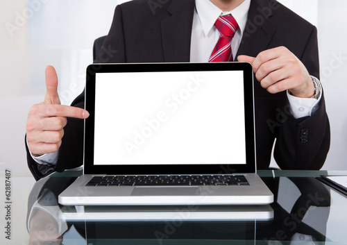 Confident Businessman Displaying Laptop At Desk