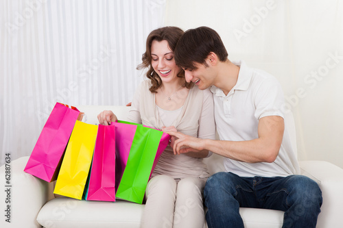 Happy couple sitting on couch with shopping bags