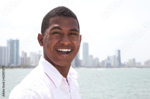 Portrait of a laughing guy at beach with skyline