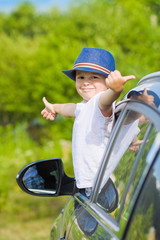 Portrait of cute boy in car showing thumbs up sign