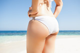 Sexy young woman in white bikini bottom standing on beach poster