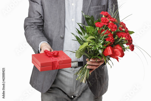 Man holding bouquet of red carnations and red gift box