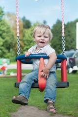 Swinging little boy in denim