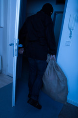 Thief Carrying Sack While Exiting House