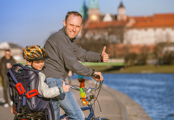Father with son riding by bicycle along the river waterfront in