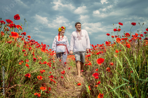 Young ukrainian couple in national clothes go through poppies fi