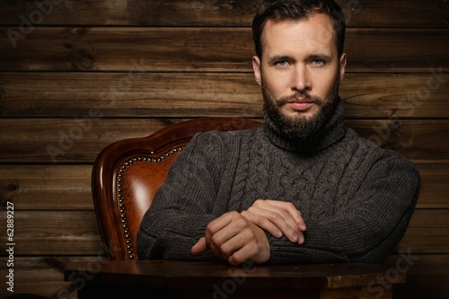 Handsome man wearing cardigan in wooden interior