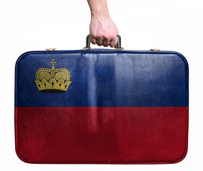 Tourist hand holding vintage leather travel bag with flag of Lie