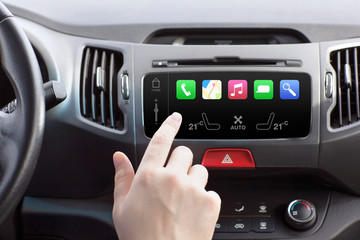 man sitting in a car and touch play finger in a auto smart syste