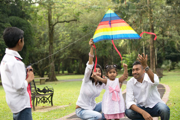 indian family playing kite in the outdoor park