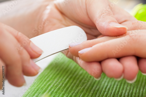 Beautician Filing Nails Of Woman