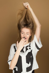 a young girl in a t-shirt playing with the hair
