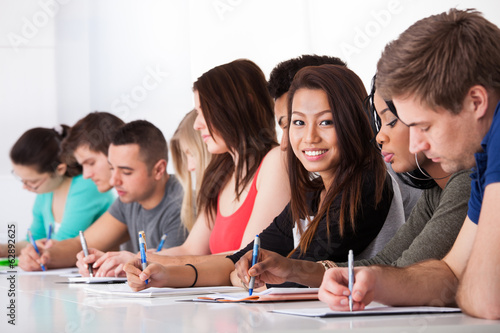 Female Student Sitting With Classmates Writing At Desk