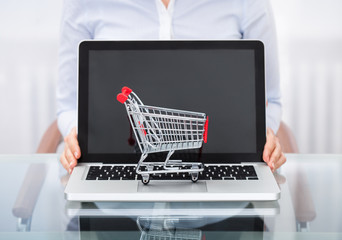 Businessperson With Shopping Cart And Laptop