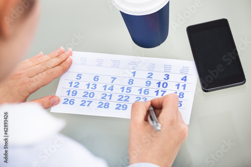 Businessperson With Pen Writing On Calendar And Cellphone