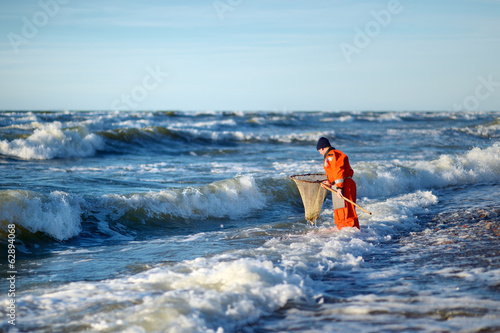 Man with landing net looking for amber on a sea