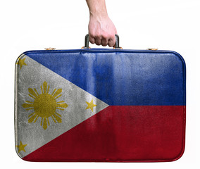 Tourist hand holding vintage leather travel bag with flag of Phi
