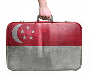 Tourist hand holding vintage leather travel bag with flag of Sin
