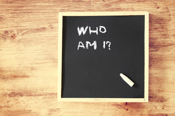 who am i concept written over chalkboard
