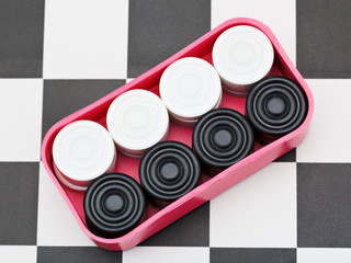 box with draughts on checkerboard