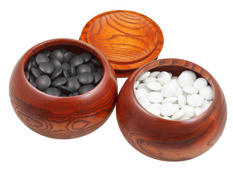 set of go game stones in wooden bowls