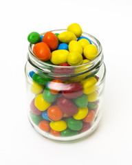 Isolated colorful candy in opened jar on white background.