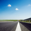 asphalt road to horizon in blue sky