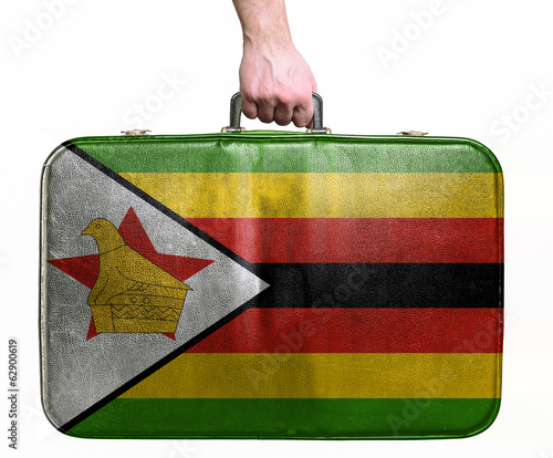 Tourist hand holding vintage leather travel bag with flag of Zim
