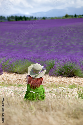 Young romantic woman sitting in front of violet lavender field i