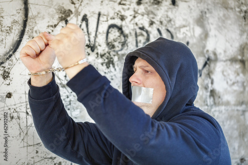 Hostage in handcuffs with tape on the mouth near wall
