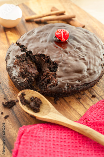 Round homemade chocolate cake on wooden background.