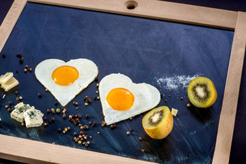 breakfast with eggs, cheese, kiwi and orange juice on chalkboard