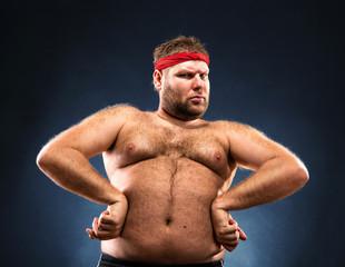 Fat man imitating muscular build studio shot