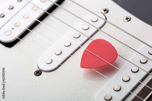 Red pick in electric guitar strings
