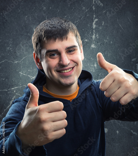 Young man giving thumb up against grungy wall
