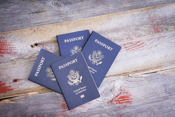 Four United States passports on a wooden table