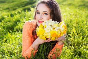 Happy smiling girl with yellow flowers daffodils