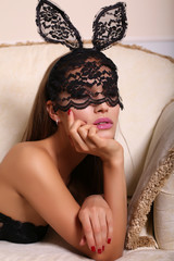 sexy woman in bunny's mask lying on the divan