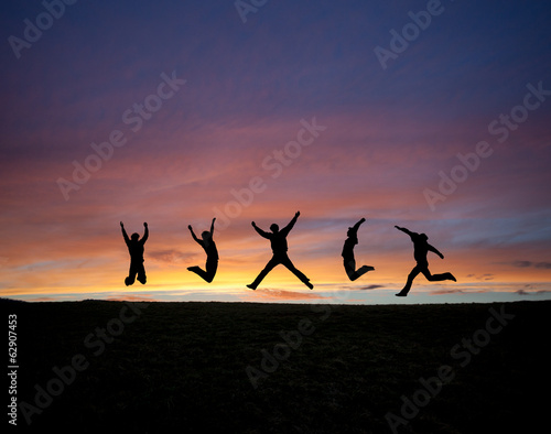 silhouetted teens jumping in sunset sky