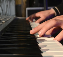 Adults fingers on the keys of a piano playing