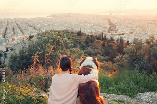 Young woman hugs her dog as they sit in a field.Athens,Greece.Re