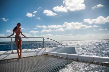 A woman holding a rail on a catamaran in the Caribbean Sea